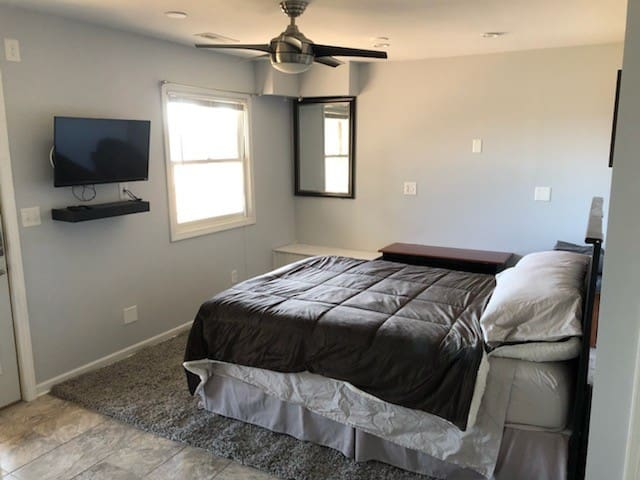 Lower level bedroom with queen bed, full bathroom, access to lower level screened in porch, and TV with a prime firestick and DVD player.