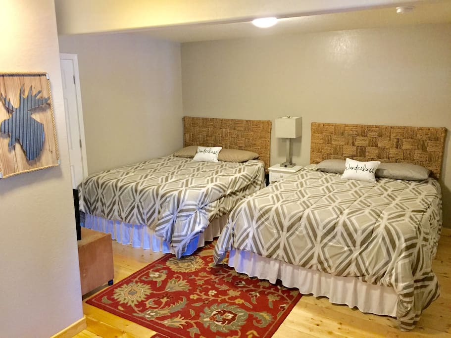 Downstairs bedroom with two queen beds and private full bath.