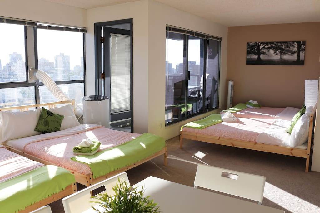 The cozy shared space has 4 double beds and access to a private balcony with stunning city views