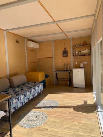 Questhouse from inside. Sofa bed, mattresses, table, fridge, open shelves, carpets, lights.