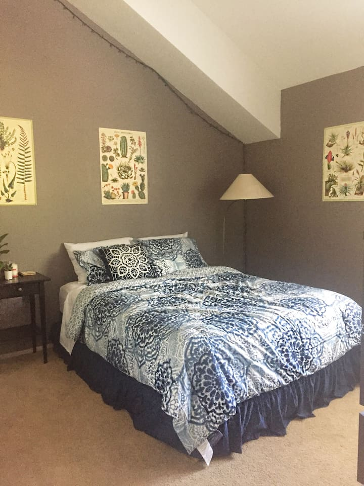 This is your room. It comes complete with a pillow-top queen bed, dresser, side table, desk fan, closet with hangers, and attached bathroom.