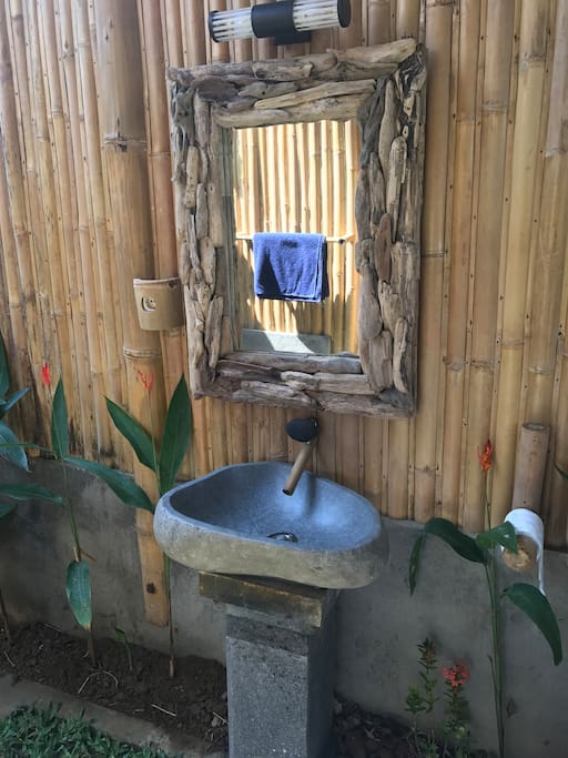 Stone and bamboo tap, stone sink with a volcanic stone pedestal