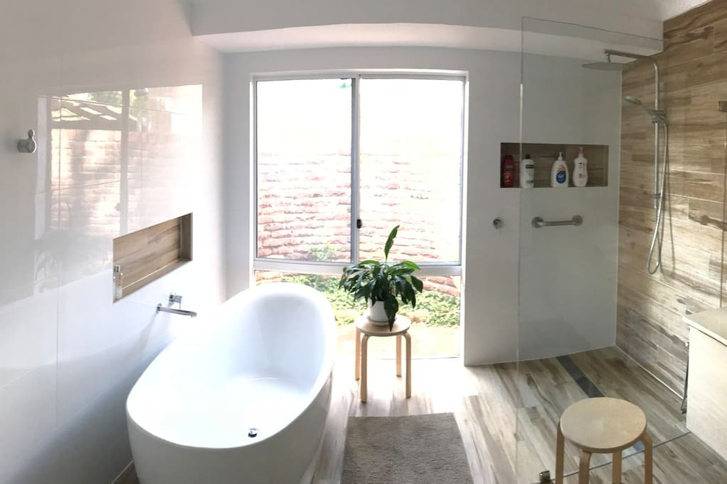A brand new contemporary bathroom has a large reclining bath or try the rain head - walk in shower.  The floors are heated, with a heated towel rail and heat lamps.   Enjoy the privacy with an enclosed circle wall and a camellia and wild strawberry garden.