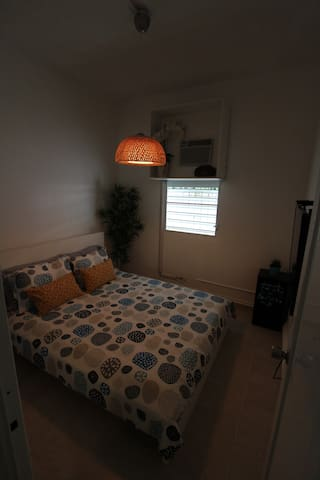 Cozy bedroom with comfortable queen sized bed, air conditioning and flat screen smart TV.