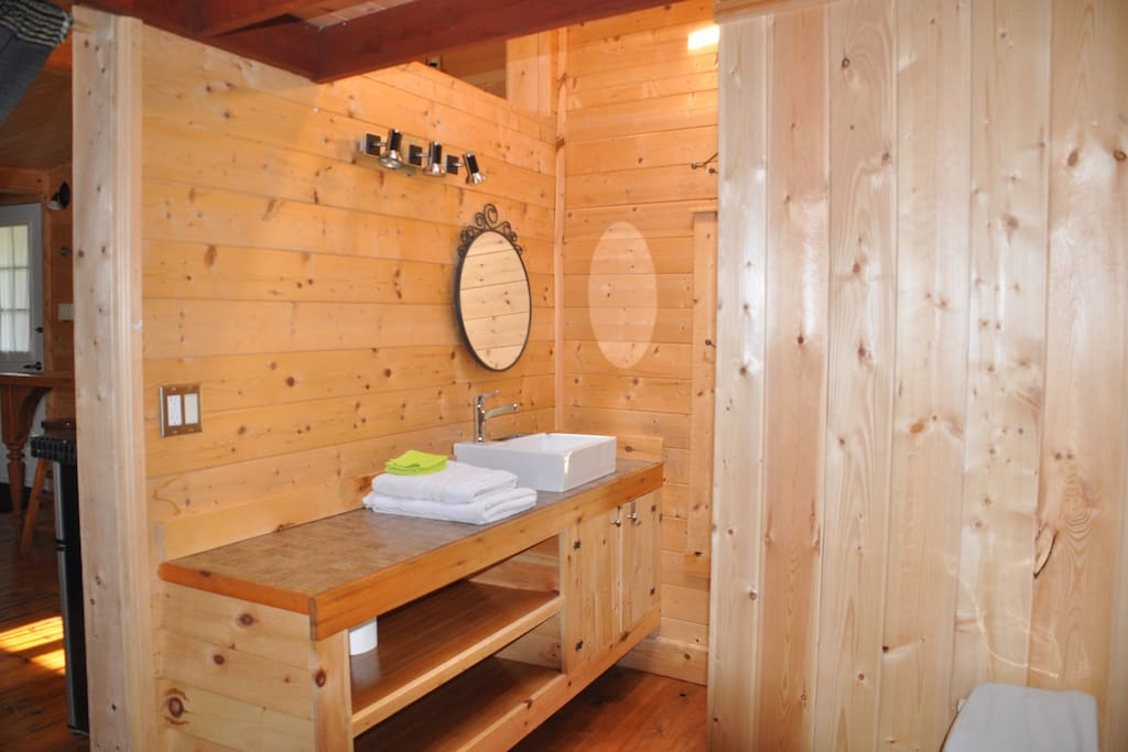 Salle de bain entièrement en bois avec puits de lumière au dessous de la douche...