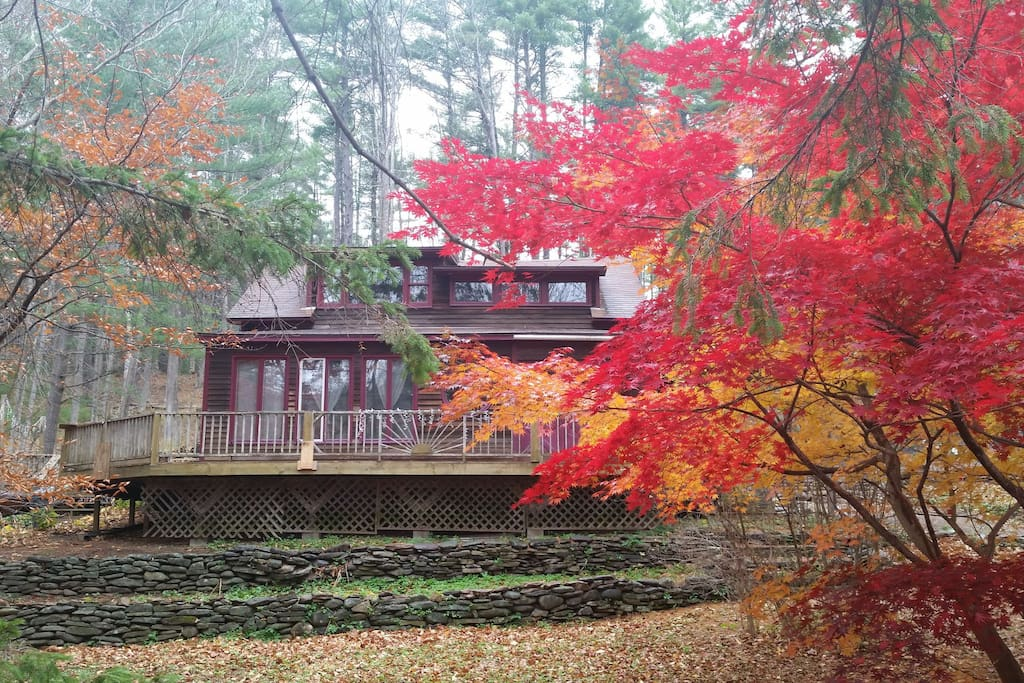 The house and deck face south with a stream across the way.