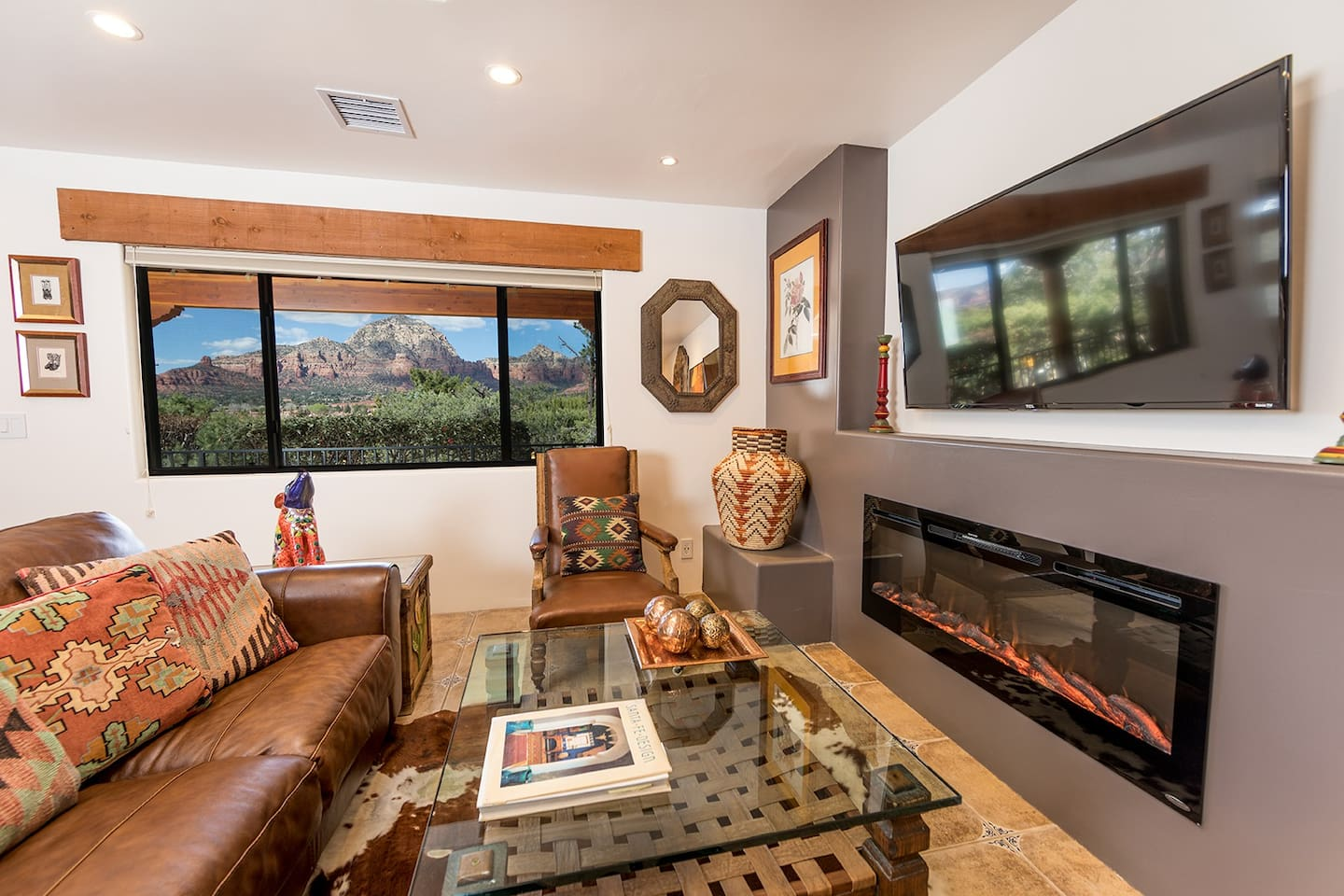 The living room has breathtaking red rock views, an electric fireplace, UHDTV, large leather sofa, desk, queen-sized Murphy bed, full kitchen and dining area.