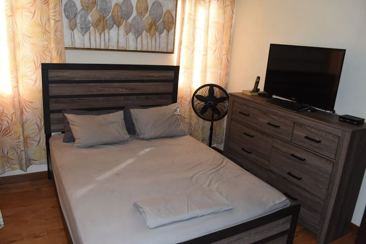 Cozy Master Bedroom with en suite shower as well as ceiling and standing fans.
