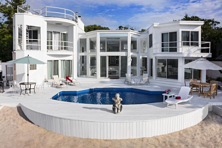 The main house at 73 Baywalk has a pool and outdoor dining.