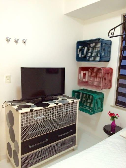 Tv, comoda para colocar roupas, ou quaisquer outros objetos de uso pessoal.