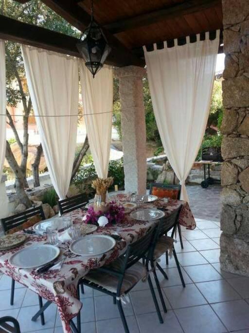 Il bellissimo patio con il tavolo apparecchiato e le tende bianche