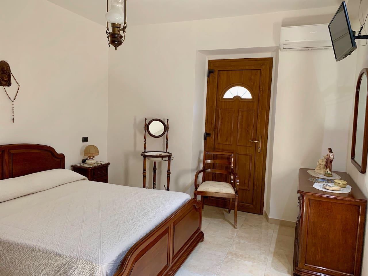 Camera con letto matrimoniale, armadio, tv e aria condizionata