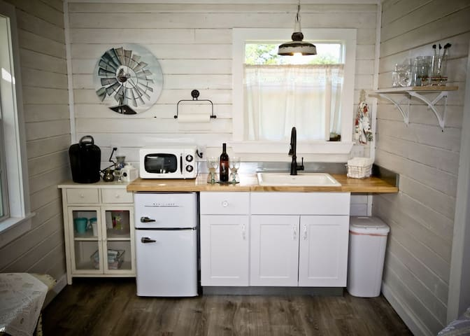 kitchenette with microwave, fridge with separate freezer, coffee station and nice sink.