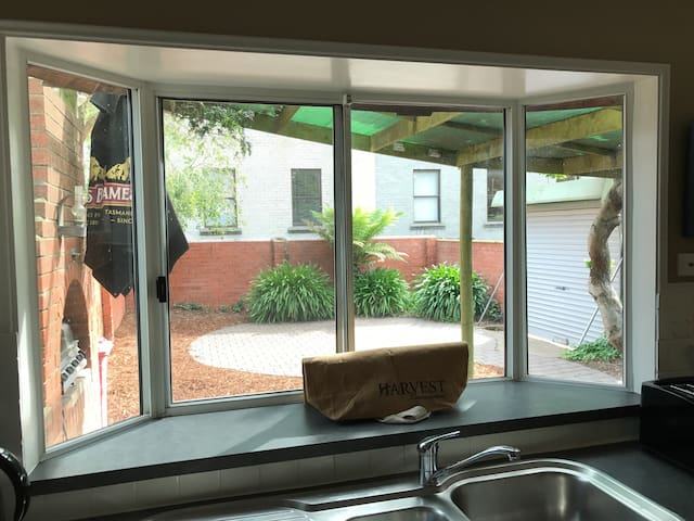 Looking out from the kitchen to a shade cloth area, BBQ space and car parking right there at the door. Rare for inner city properties!