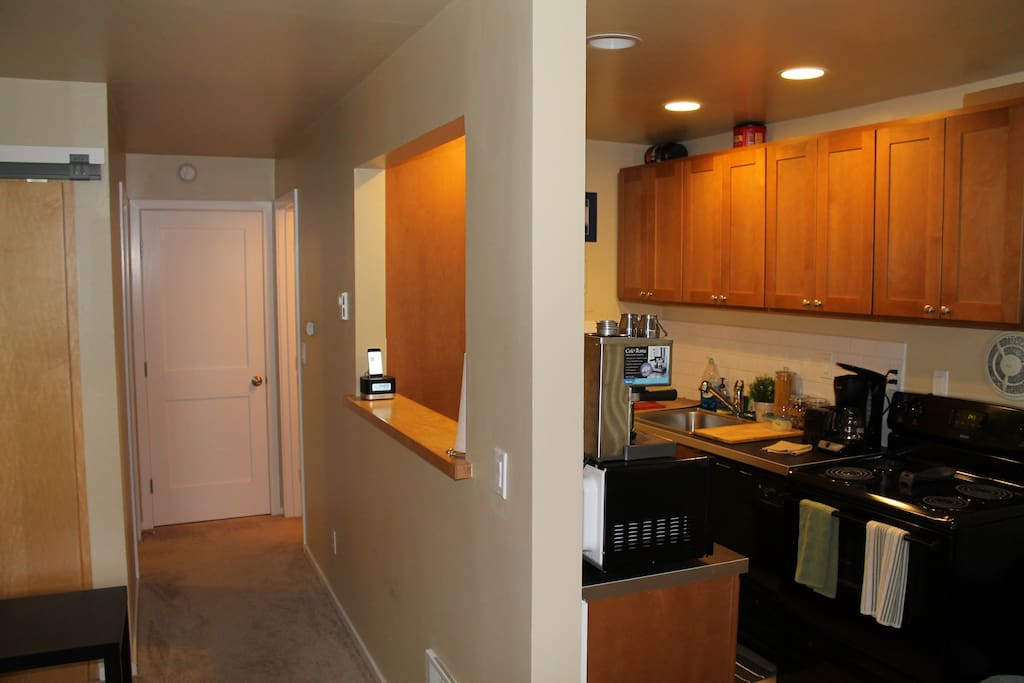 view of kitchen and hallway from entryway area. Bathroom is on the right down the hall, bedroom on the left.