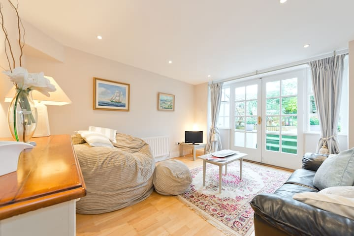 Bright and airy living room and TV lounge open onto a private garden and small deck.
