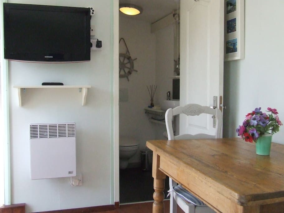 The TV, ensuite and dining area