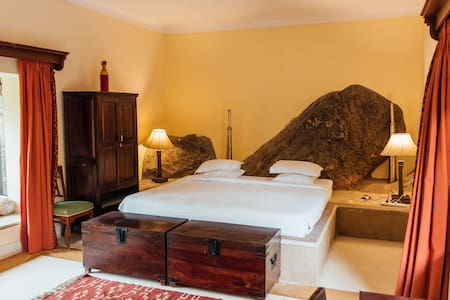 A room built out of the rock with a swimming pool