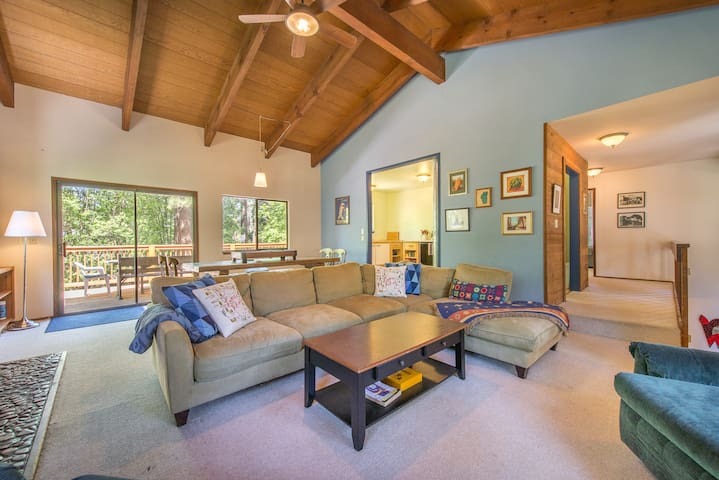 Large open great room with vaulted ceilings, flat screen TV, fireplace and large dining table!
