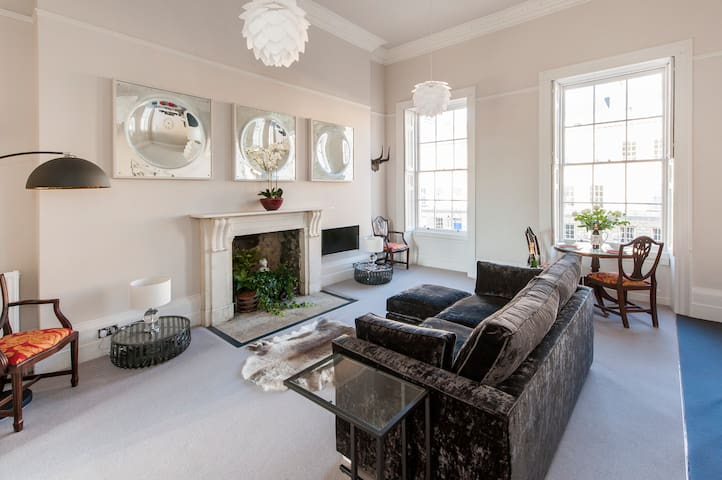 Three large concave mirrors bounce the light around the bright living room.