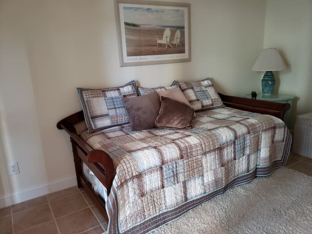 A trundle bed gives two twin beds in this bedroom/rec room. Private, full bathroom, too!