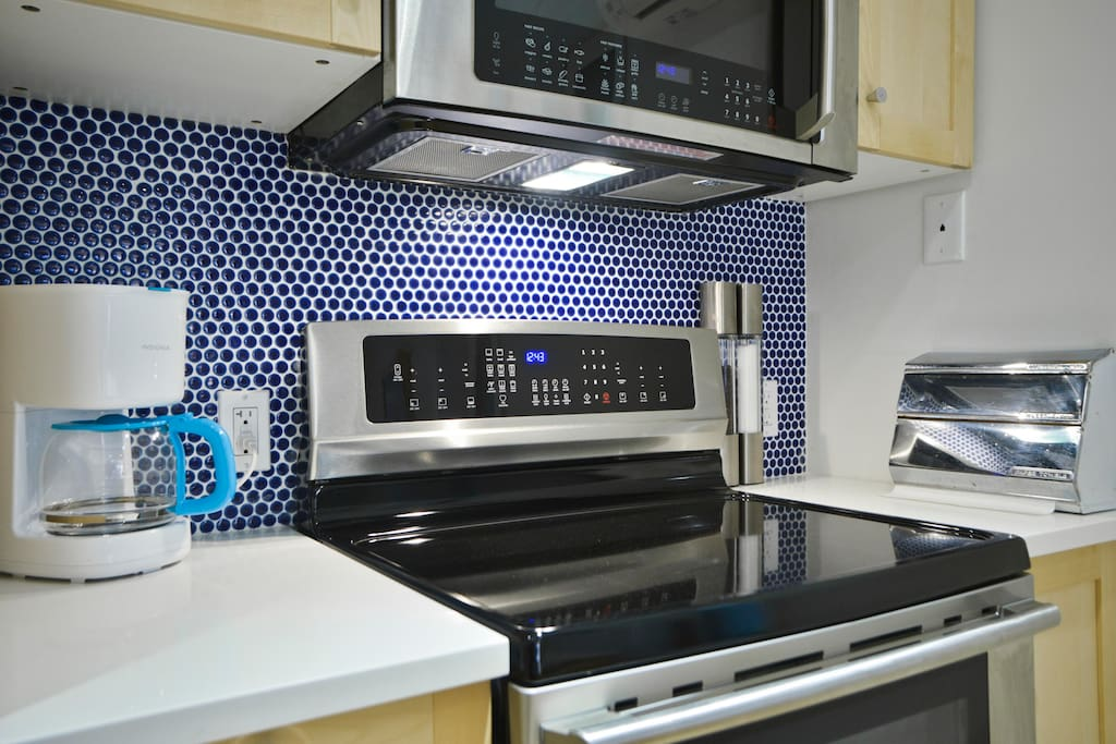 Fully equipped kitchen with induction stove, microwave/speed oven, coffee maker, dishwasher and refrigerator/freezer