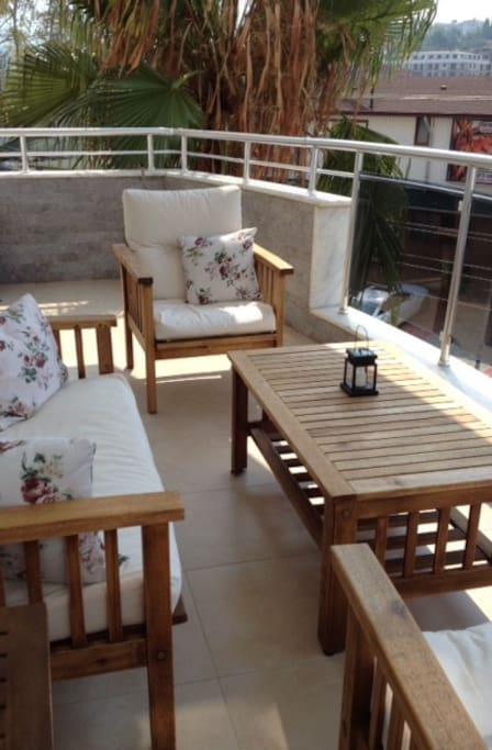 Balcony with comfortable sitting area and nice view.