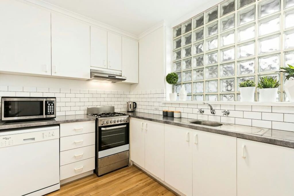 Bright, fully equipped kitchen with microwave, dishwasher, oven, stove and fridge.