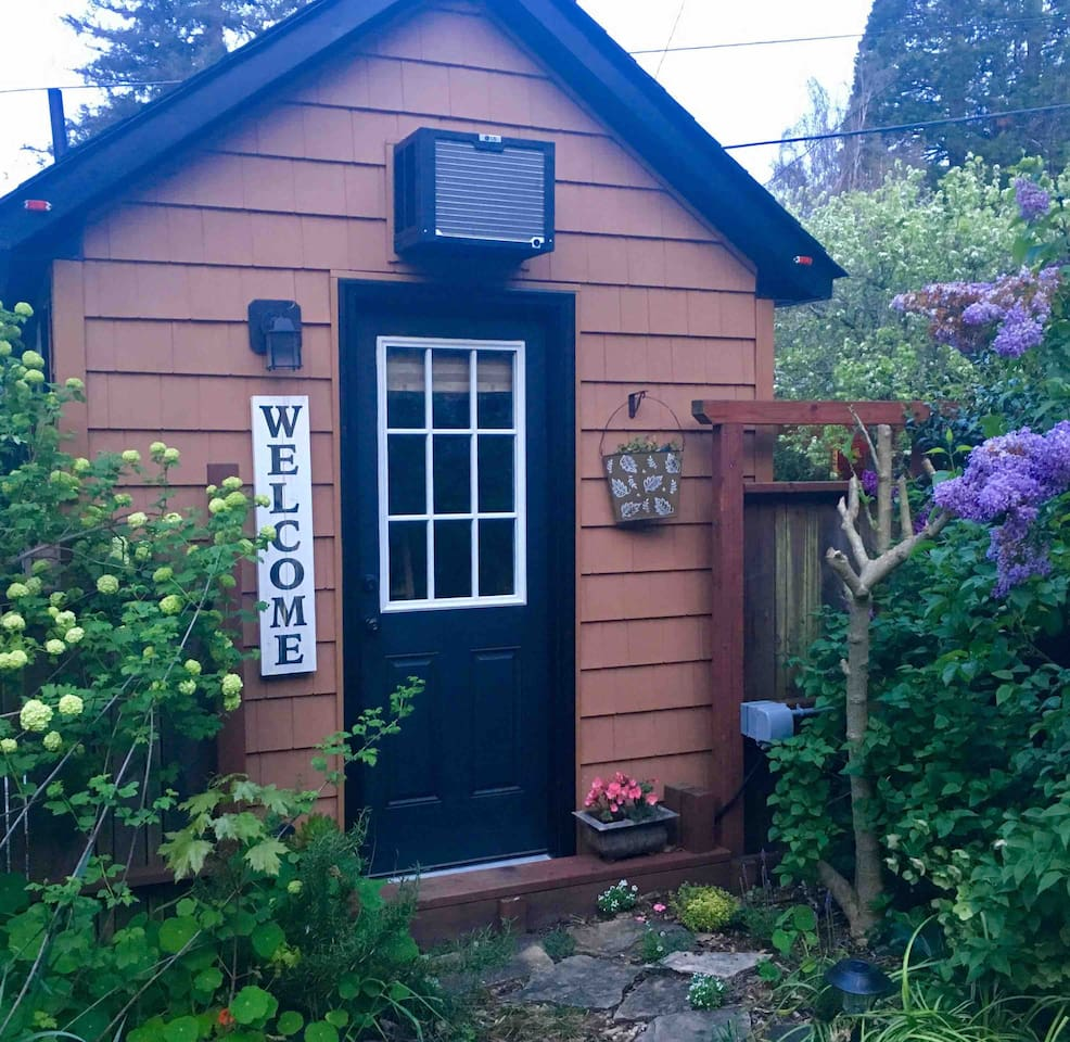 C'mon in and live large in Jenny, my tiny house RV in a lush garden