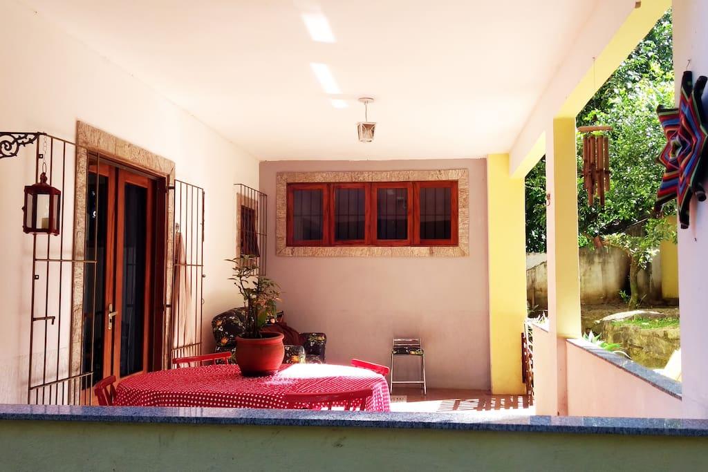 Varandinha com sol da manhã, rede, mesa e sofá.