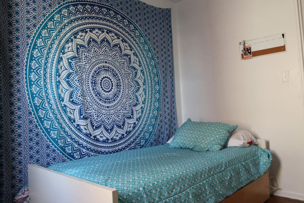 Mandala tapestry on the wall, comfortable single bed.