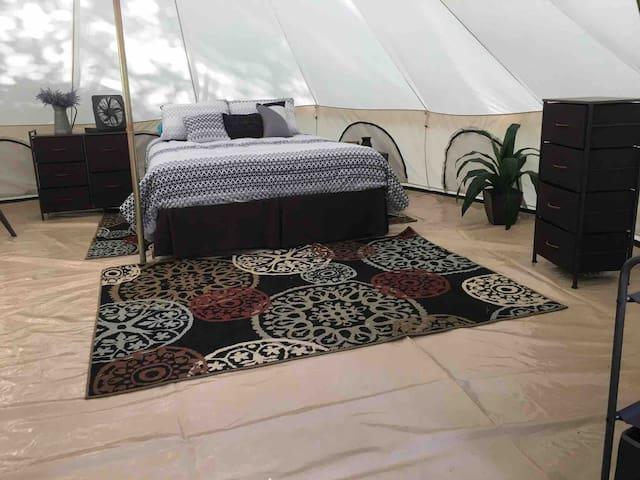 Wonderful queen sized bed, fan, tables, in a warm setting.