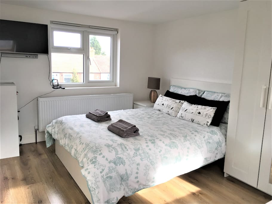 Double bed with TV and side window over looking garden - viewing by the small dinning table.
