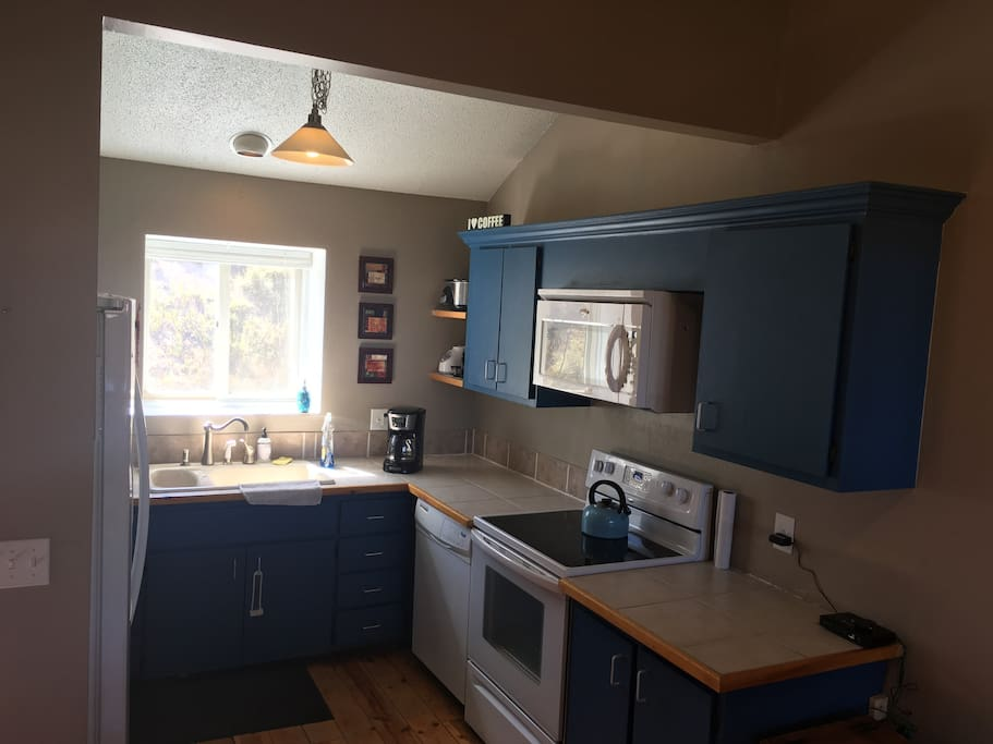 Fully equipped kitchen with all your necessities -blender, pots, pans, spices, coffee maker, tea kettle, crock pot, silverware and dining