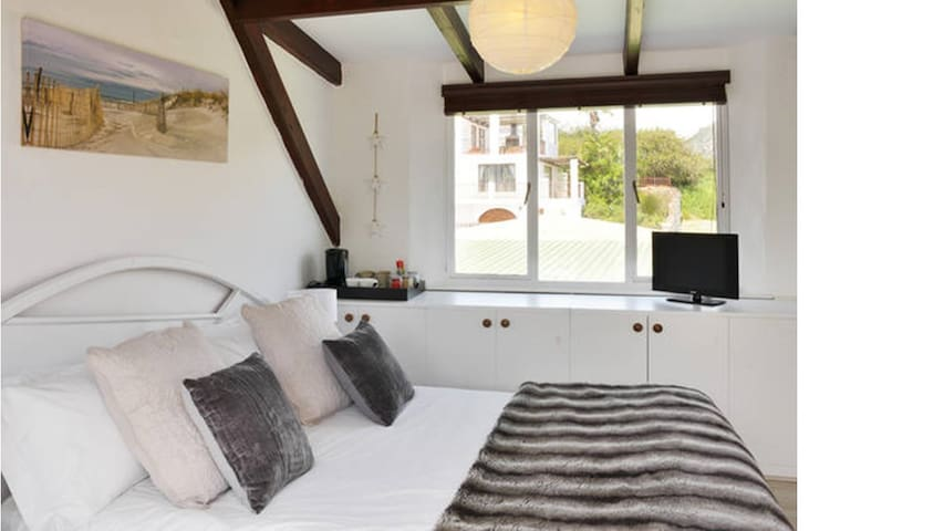 The loft room has an extra length queen sized bed and lots of cupboard space. There is a tea and coffe tray and a TV with the full bouquet of DSTV.