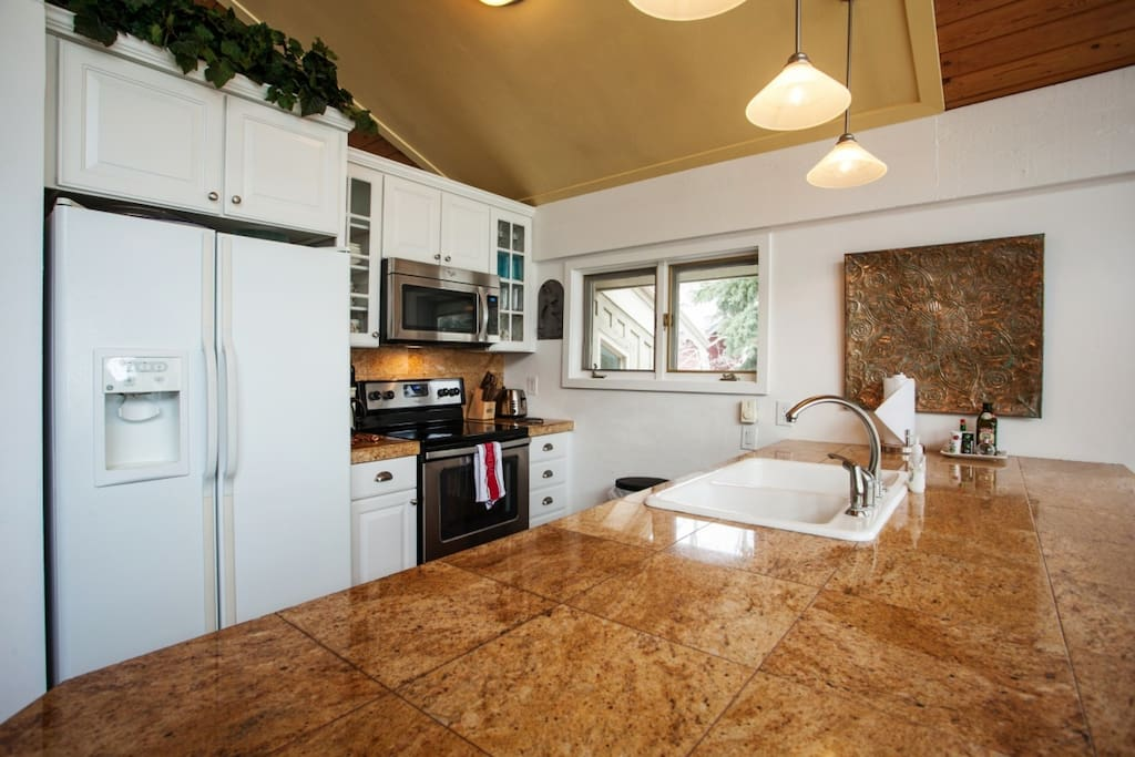 Open kitchen with stainless appliances and bar seating for 2.
