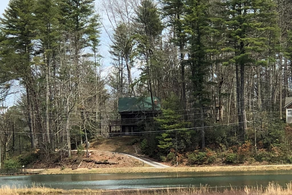 First view of the cabin as you drive around the lake. The home overlooks a small lake and is surrounded by trees, mountains and wildlife.