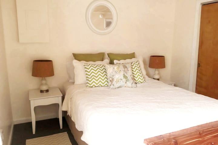 Bedroom with queen bed, closet, and dresser