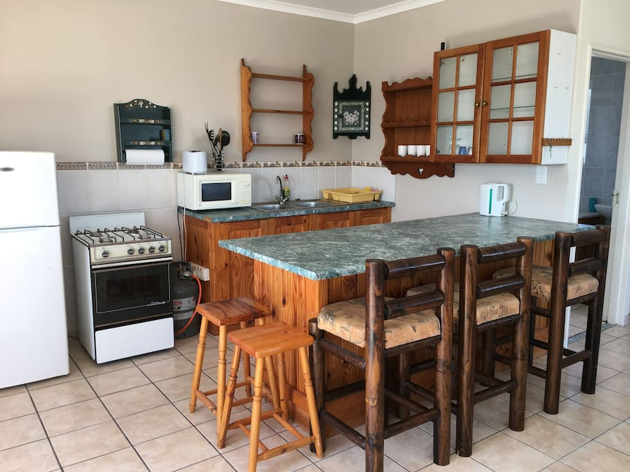 The kitchen is fully equipped with fridge, gas stove and microwave. The spacious breakfast bar is perfect for entertaining guests and eating meals.