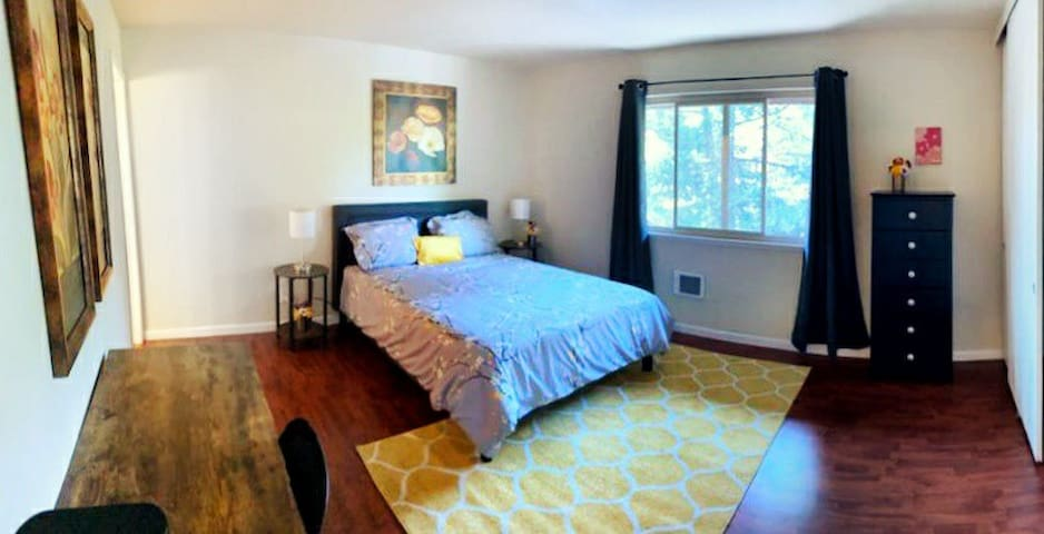 Master bedroom with large window to let in light, but also with black out curtains to block light when needed.   Large desk and chair provides the perfect work space.