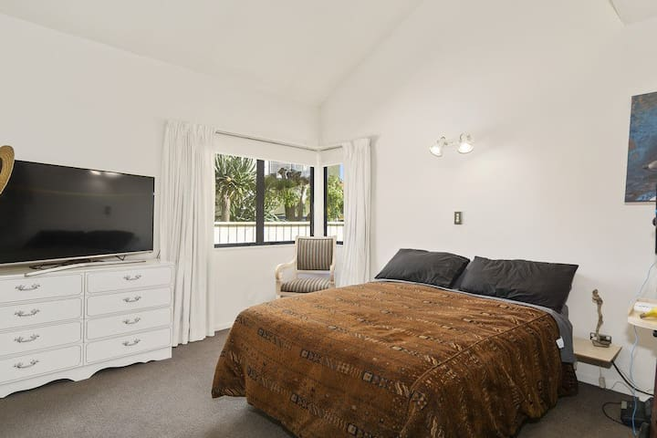 Queen bed in large room with TV, seating and workspace.