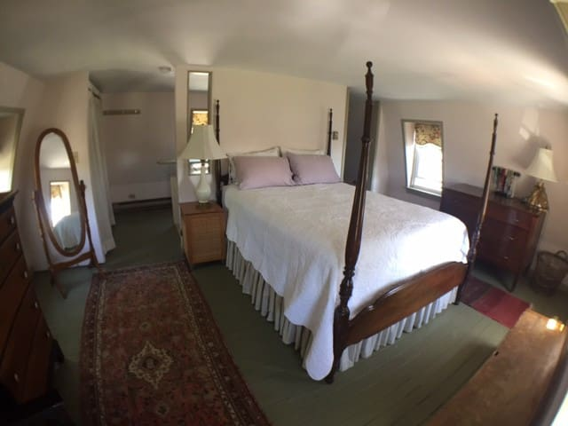 Front bedroom with queen bed and half bath, breezy with 5 windows!