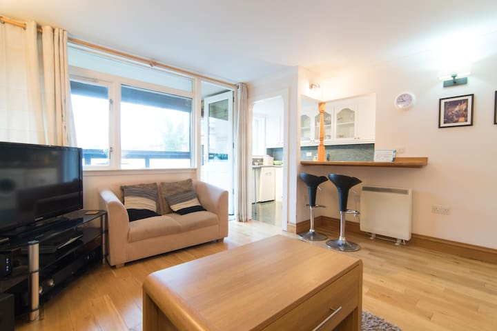 Relax and enjoy my spacious living room, including an open plan kitchen/breakfast bar as well as bright balcony with table and chairs.