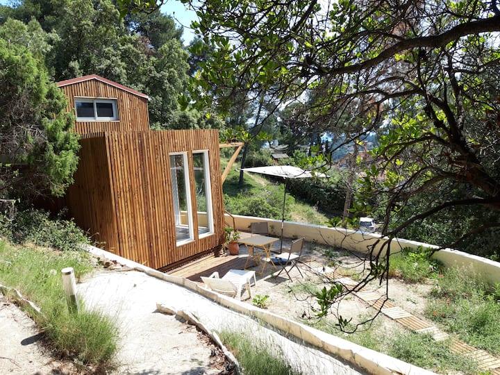 Studio de jardin sur colline arborée vue mer