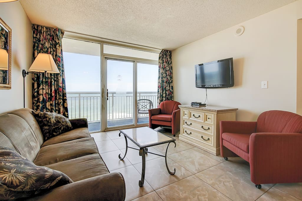 Overlooking the ocean, the living room offers direct access to the private balcony.