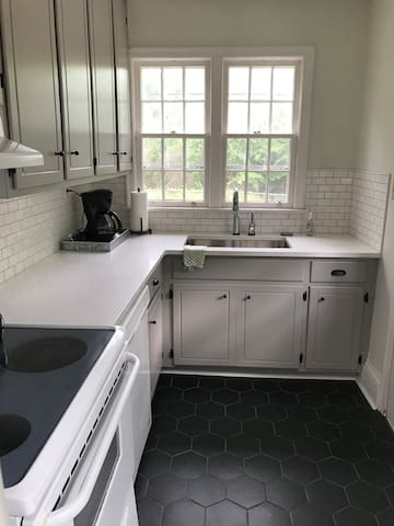 Updated galley kitchen with quartz counters, full size stove, and refrigerator.