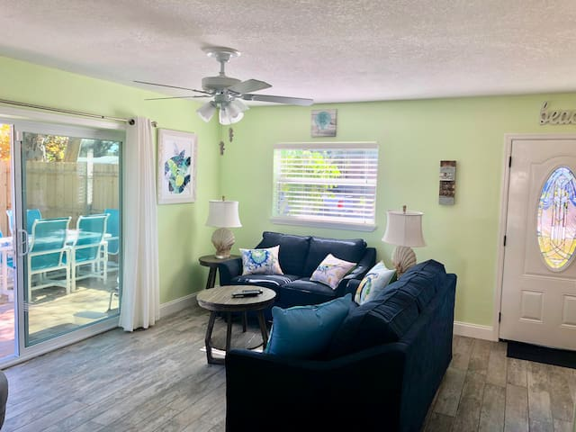 Living room with a patio off the side - equipped with propane BBQ and an outdoor dining table/chairs to seat six people.