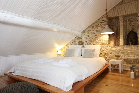 The large double bed sits against an original, stone wall adding a rustic and traditional feel to the studio