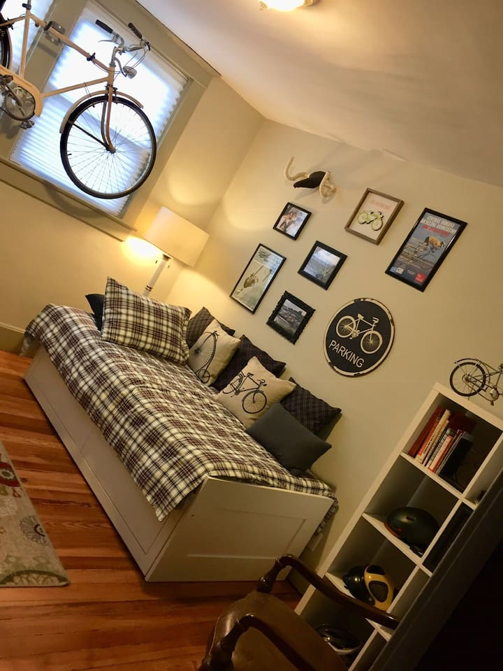This is the Bike Room. It has as one-person day bed with a pullout that can accommodate two guests. It's a 10' x 10' room. There is a desk and 2 chairs, along with a bookcase and continental breakfast and coffee/tea supplies (with a hotpot).