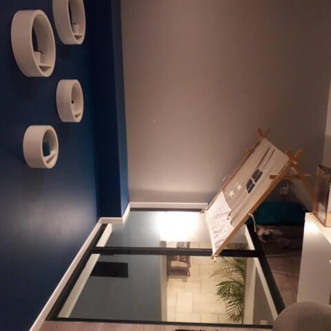 mezzanine avec vitre au sol donnant sur le salon